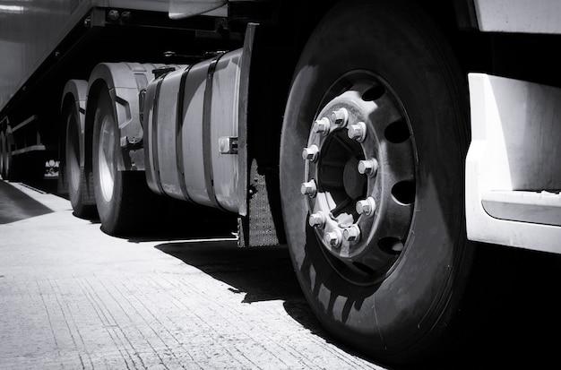 Truck transportation, close up truck wheel semi truck parked in depot. Premium Photo