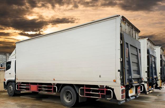 夕焼け空の駐車場のトラックコンテナー。道路貨物業界の配送物流と輸送。 Premium写真