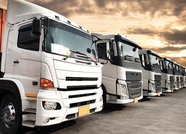 Trucks parked lined up at sunset sky, road freight industry logistics and transport Premium Photo