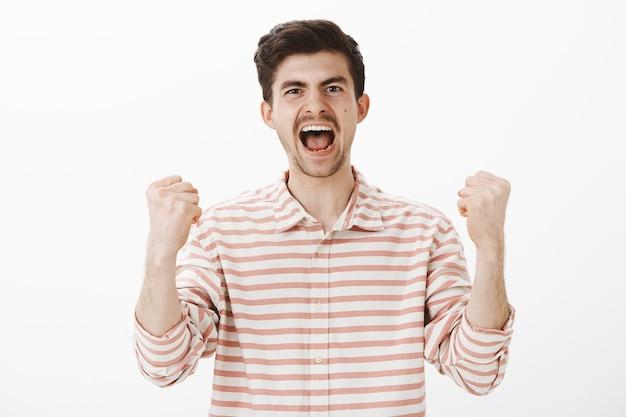 Vero tifoso gioioso per la sua squadra del cuore. colpo di trionfante bel collega maschio, urla di felicità e vittoria, alzando i pugni chiusi, celebrando la vittoria, sentendosi come un campione sul muro grigio Foto Gratuite