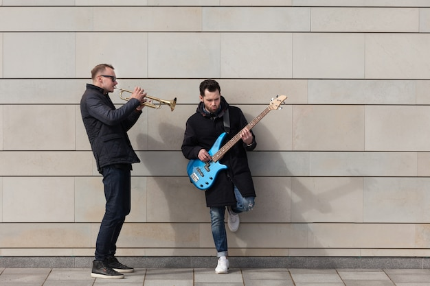 Trumpet player and guitarist playing in front of wall Free Photo