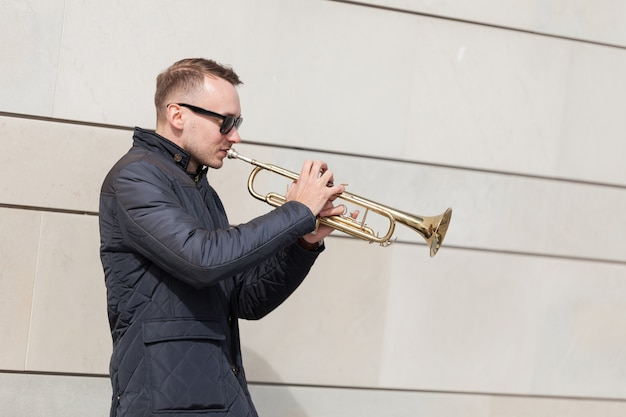 Trumpet player playing outdoors Free Photo