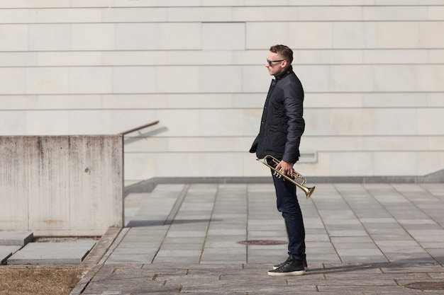 Trumpet player in urban environment side view Free Photo
