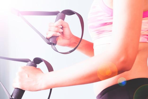 ボディービルディング。 trxストラップで運動する強いフィット感の女性。 無料写真