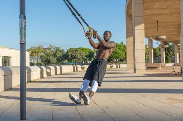 システムtrxによる男性の筋肉トレーニング Premium写真