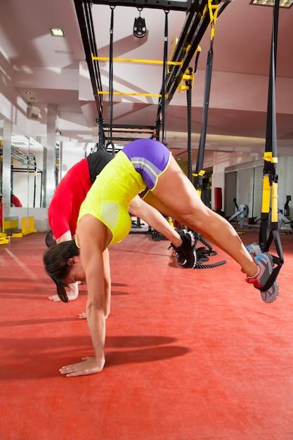 ジム女と男でフィットネスtrxトレーニング演習 Premium写真