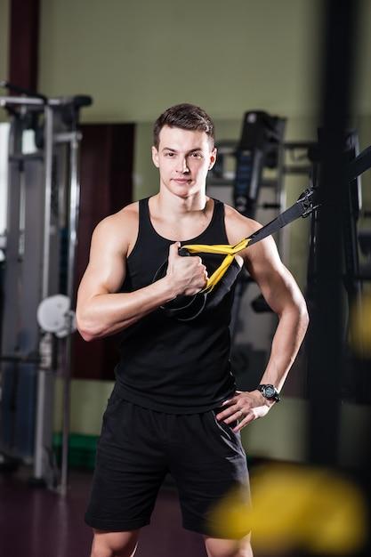 若い男はtrxのスポーツホールに従事しています。 Premium写真