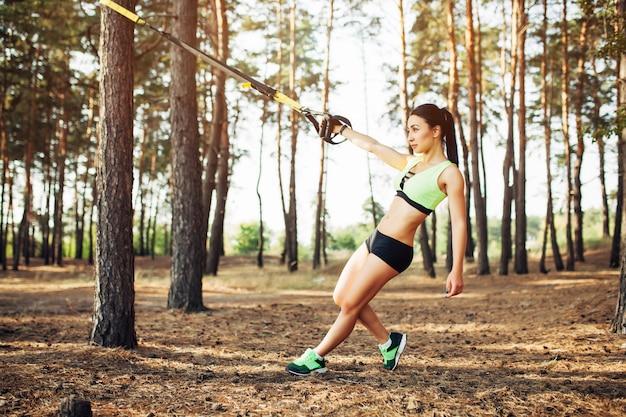 屋外で健康的なサスペンショントレーナースリングとtrx運動をしている美しい若い女性 Premium写真