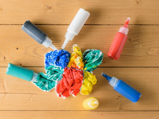 Tubes of fabric paint and a painted t-shirt on a wooden table. Premium Photo