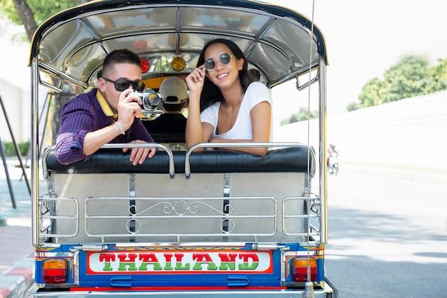 Молодая пара туристов, путешествующих на местном такси tuk tuk в бангкоке, таиланд Premium Фотографии