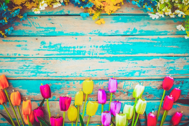 Tulip blossom flowers on vintage wooden background, border  frame design. vintage color tone - concept flower of spring or summer background Premium Photo