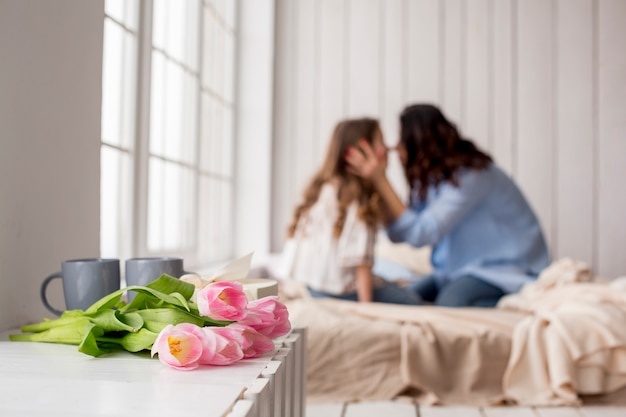 Tulip flowers on table near bed with hugging mother and daughter Free Photo