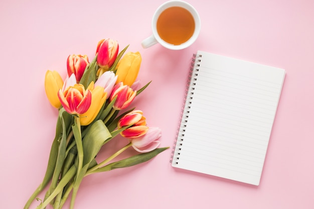Tulip flowers with notebook and tea cup Free Photo