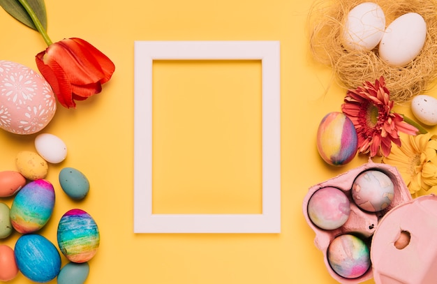 Tulip; gerbera flower; easter eggs and empty white border frame on yellow background Free Photo