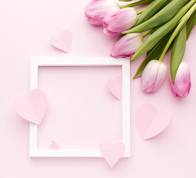 Tulips bouquet on table beside frame Free Photo