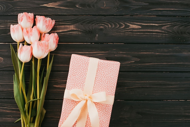 Tulips bouquet with gift box on wooden table Free Photo