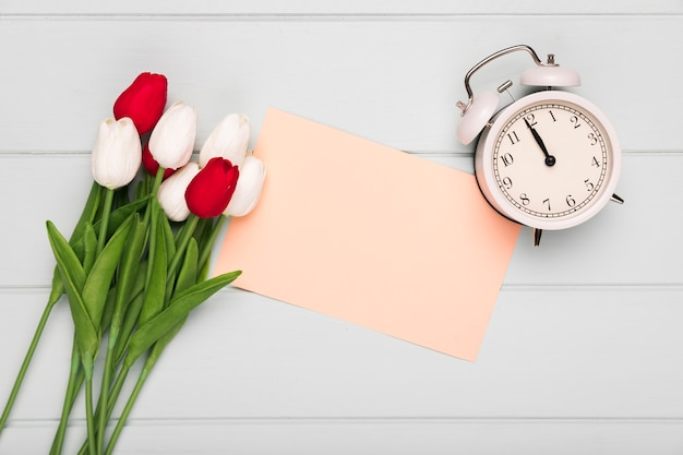 Tulips bouquet with greeting card beside and clock Free Photo