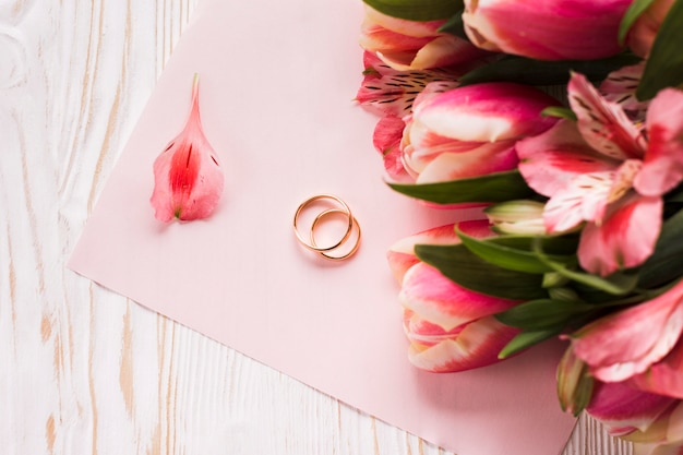Tulips on table beside engagement rings Free Photo
