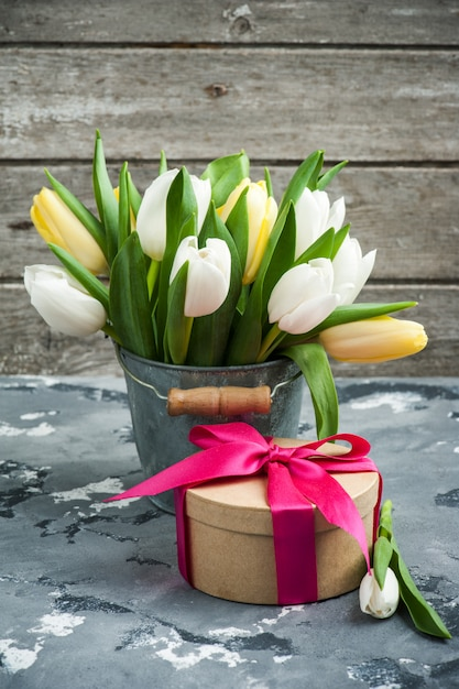 Tulips in tin bucket and a gift package Premium Photo