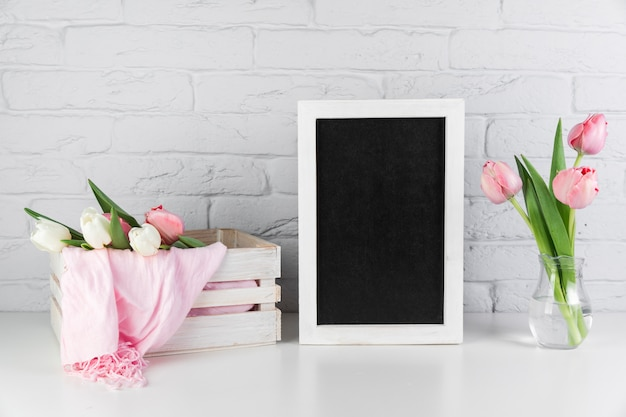 Tulips vase and crate near the blank black white border frame on desk against brick wall Free Photo