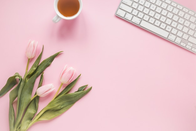 Tulips with tea cup and keyboard Free Photo