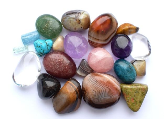 Вываливались драгоценные камни разных цветов. аметист, розовый кварц, агат, апатит, авантюрин, оливин, бирюза, аквамарин, горный хрусталь. Premium Фотографии