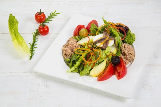 マグロ、アンチョビ、卵。グリーンビーン、白い皿に甘い黄ピーマン、赤玉ねぎ、ブラックオリーブ、トマトのおいしいサラダのスライス Premium写真