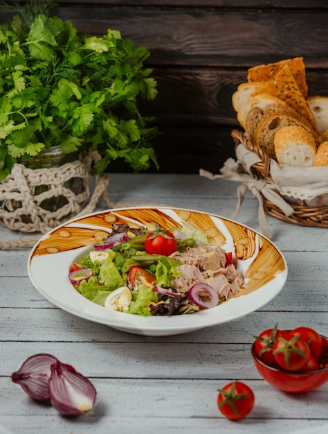 Tuna salad with boiled eggs, lettuce, green beans, tomatoes, onion and corn Free Photo