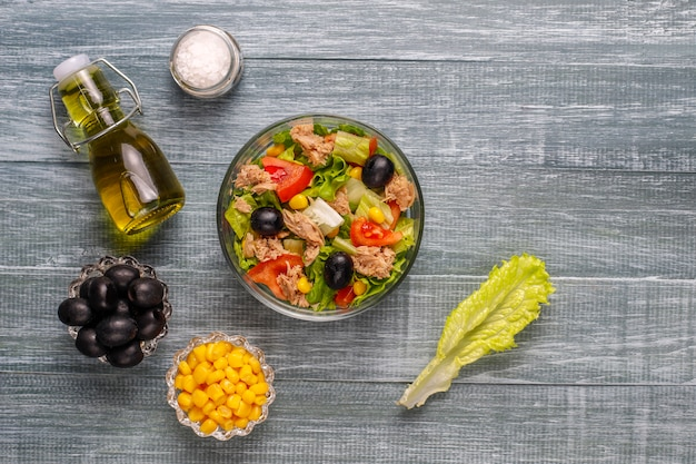 Tuna salad with lettuce, olives, corn, tomatoes, top view Free Photo