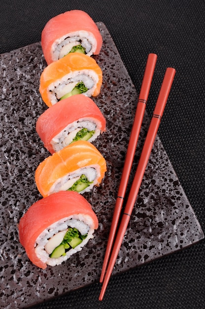 Tuna sushi roll with chopsticks on a black plate Free Photo