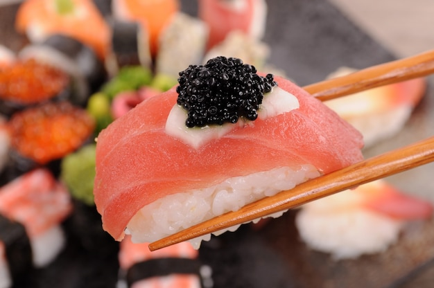 Tuna sushi with caviar held by chopsticks Free Photo