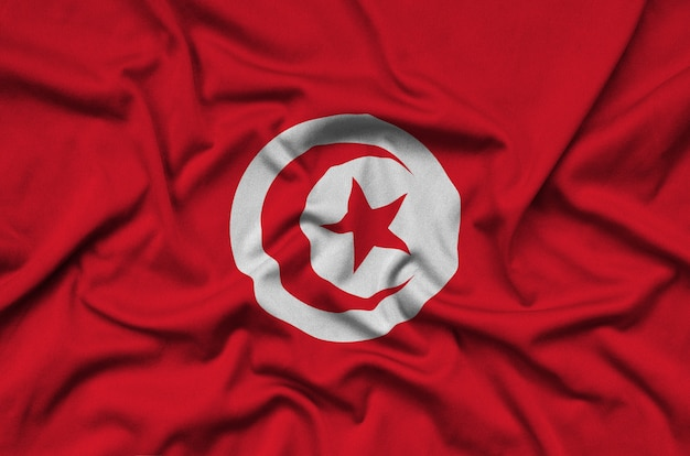 Tunisia flag  is depicted on a sports cloth fabric with many folds. Premium Photo