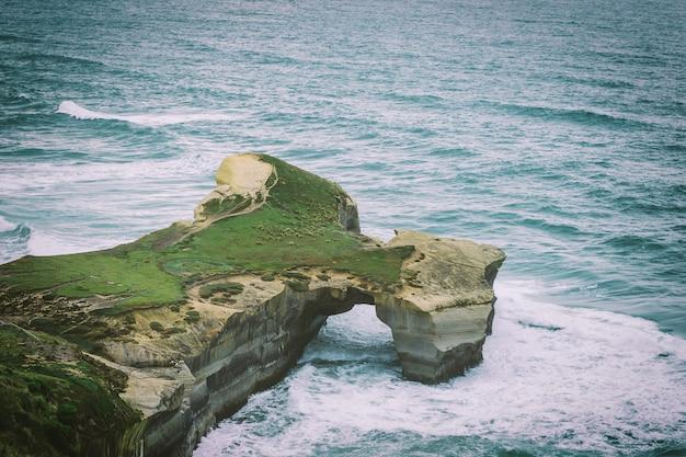 ニュージーランドのダニーデン近くのトンネルビーチと砂の崖 Premium写真