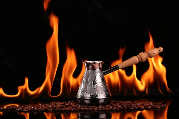 Turk on coffee beans on a background of fire, black background. concept vivacity and energy Premium Photo