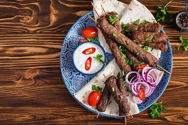 Premium Photo Turkish And Arabic Traditional Ramadan Mix Kebab Plate Kebab Adana Chicken Lamb And Beef On Lavash Bread With Sauce Top View