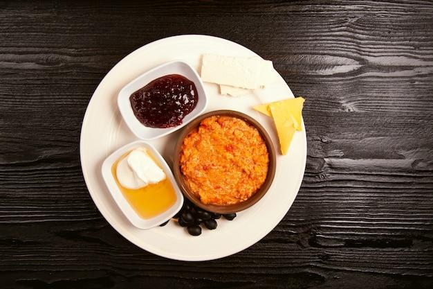 Турецкий завтрак по меню с медом, сливками, оливками, вареньем и сыром в белой тарелке и стаканом чая Бесплатные Фотографии