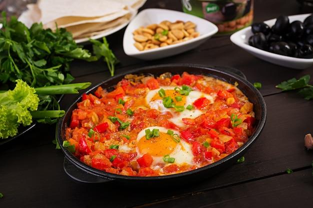 Turkish breakfast -  shakshuka, olives, cheese and fruit. Premium Photo