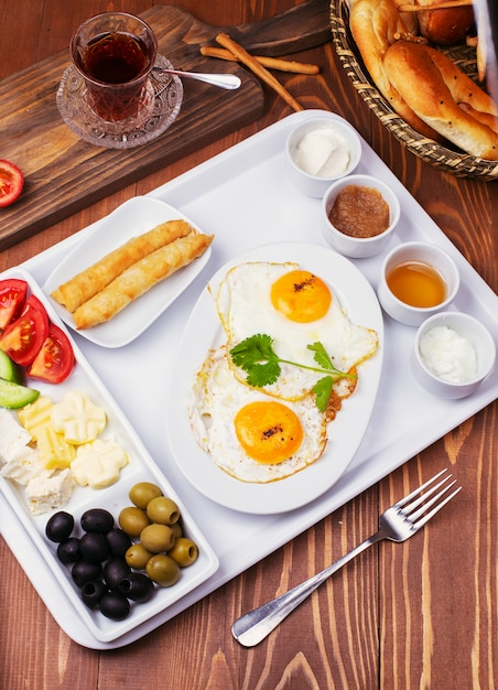 Turkish breakfast with fried eggs, tomato, cucumber, cheese varieties, black green olives, honey, jam, cream cheese, galeta bread and glass of tea Free Photo