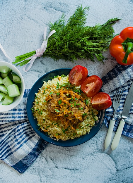 Turkish bulgur pilaf with meatballs and greens. Premium Photo