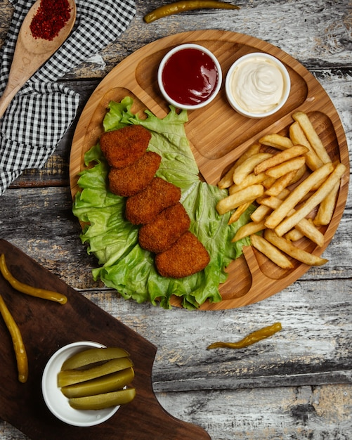 Turkish chig kogte in lettuce iwht french fries and sauces. Free Photo