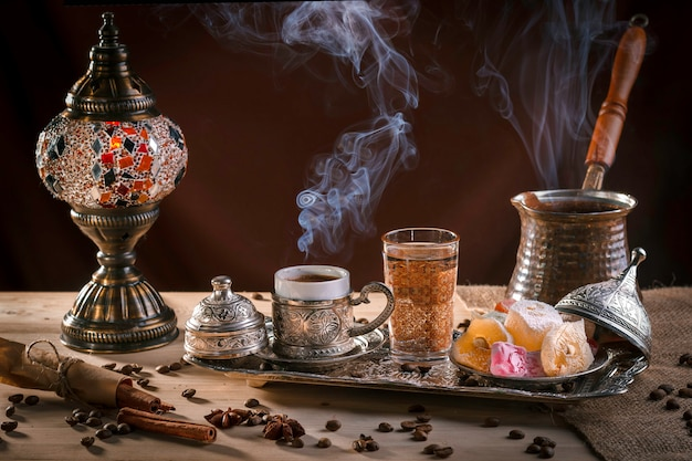 Turkish coffee in cezve and traditional turkish delight. steam over a cup. antique lamp Premium Photo