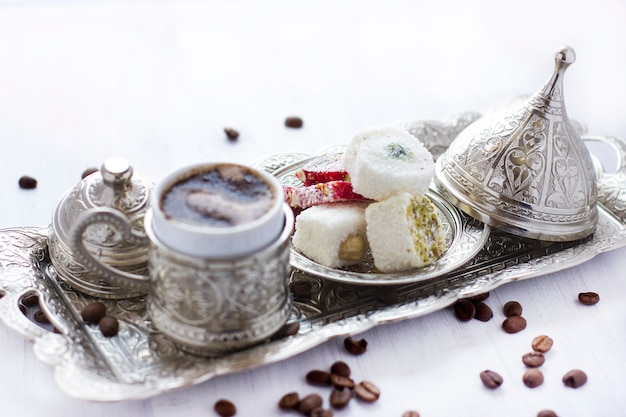 Turkish coffee with traditional turkish sweets in silver mug. selective focus. Premium Photo