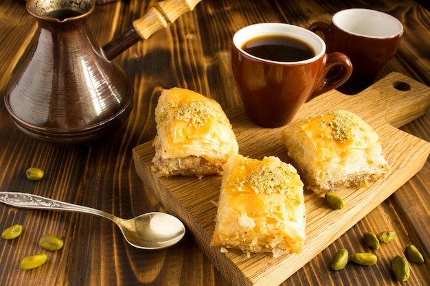 Turkish delight and  coffee on the cutting board on the  brown  wooden background Premium Photo
