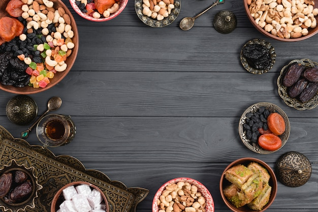 Turkish delight lukum; baklava; dried fruits and nuts on wooden backdrop with space in the center for writing the text Free Photo