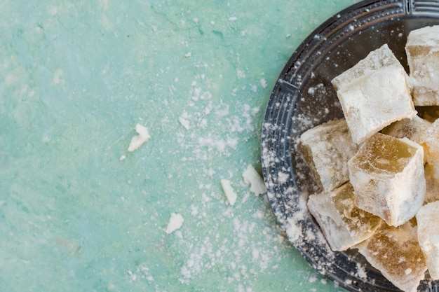 Turkish delight on plate on blue table Free Photo