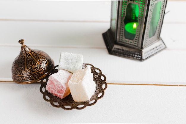 Turkish delight on plate with lid and candlestick Free Photo