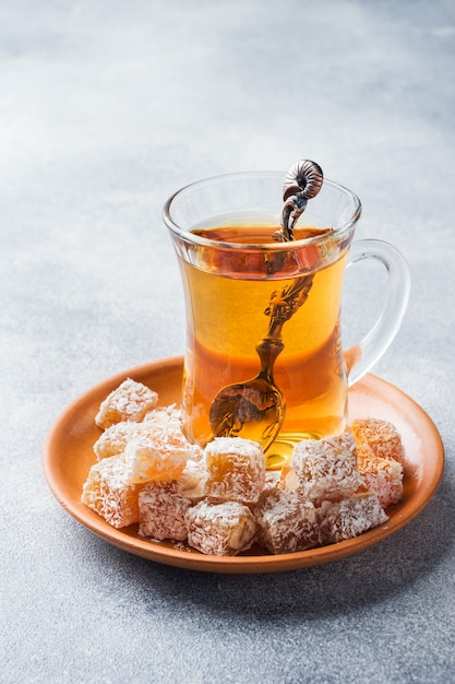 Turkish delight with hazelnut in carved metal bowl and tea in glass cup Premium Photo