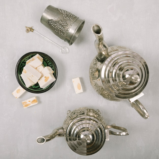 Turkish delight with teapots on light table Free Photo