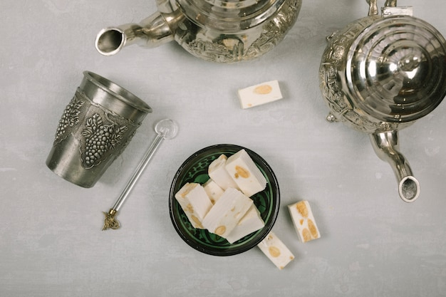 Turkish delight with teapots on white table Free Photo