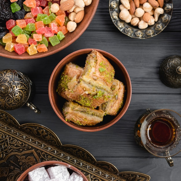 Turkish dessert baklava with dried fruits and nuts on wooden desk Free Photo